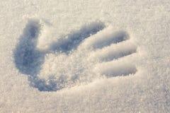 Handprint sur le blanc avec une tonalité bleue de neige avec un hiver d ensoleillé Photos stock