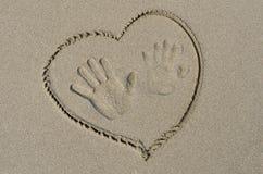 Handprints и сердце нарисованные на песке Стоковое фото RF