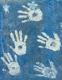 Handprints blancs de peinture sur un mur de bleu de ciel Photos stock
