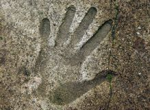 Handprints In Cement. Human handprint in old weathered concrete floor Royalty Free Stock Photos