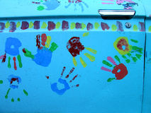 Handprints Closeup on Car Door. Handprints of colorful painted hands on car door Stock Photos