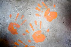 Handprints. Handprints on the concrete floor are made with orange paint stock image
