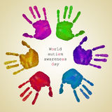 Handprints of different colors and text world autism awareness d. Some handprints of different colors forming a circle on a beige background and the text world Stock Image