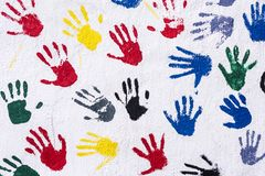 Handprints in yellow, blue, red, green, black on a white wall, background. Colorful Hhands on White wall, Concept, teamwork royalty free illustration