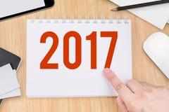 Handpunt bij het jaaraantal van 2017 op notitieboekje en technologieapparaat Stock Fotografie
