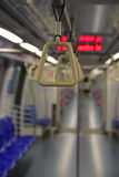 A handrail in focus inside a train designed to be grasped by standing passengers to provide support Stock Photo