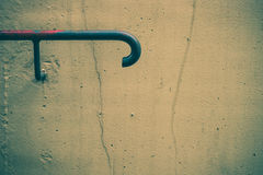 Handrail. With peeling paint attached to cracked grunge beige cement wall Stock Images