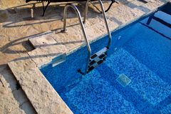 Handrail on pool. Swimming pool with stair at tropical resort. Pool handrails view. Water swimming pool with sunny reflection. Steel handrail, swimming, summer royalty free stock photos