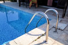 Handrail on pool. Swimming pool with stair at tropical resort. Pool handrails view. Water swimming pool with sunny reflection. Steel handrail, swimming, summer royalty free stock images
