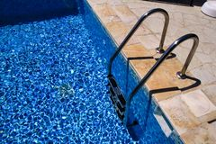 Handrail on pool. Swimming pool with stair at tropical resort. Pool handrails view. Water swimming pool with sunny reflection. Steel handrail, swimming, summer stock images