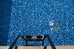 Handrail on pool. Swimming pool with stair at tropical resort. Pool handrails view. Water swimming pool with sunny reflection. Steel handrail, swimming, summer stock photography