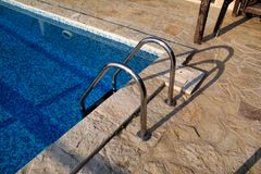 Handrail on pool. Swimming pool with stair at tropical resort. Pool handrails view. Water swimming pool with sunny reflection. Steel handrail, swimming, summer royalty free stock photography