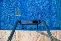 Handrail on pool. Swimming pool with stair at tropical resort. Pool handrails view. Water swimming pool with sunny reflection. Steel handrail, swimming, summer stock photos
