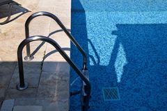 Handrail on pool. Swimming pool with stair at tropical resort. Pool handrails view. Water swimming pool with sunny reflection. Steel handrail, swimming, summer stock photo