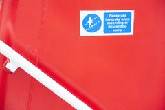 Handrail stairs steps hand rail safety sign red background on ship ferry airplane. Uk royalty free stock photos