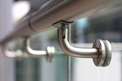Frameless Glass Fitting for Handrail. Handrail Support made of Stainless Steel fixed with Glass in close up view. A beautiful Architectural Design royalty free stock photos