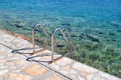 Handrail swimming on the beach of the sea. Steel handrail, swimming, blue sea, seaside, waves, summer, travel, natural environment, Mediterranean, Adriatic sea stock images
