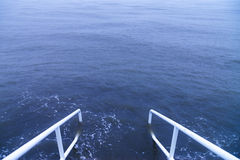 Handrails into the Sea. White handrails alongside steps that lead into a blue stormy sea Royalty Free Stock Photography