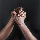 Hands. Two adult men shaking hands  close-up against black background Stock Photos