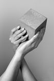 Hands. Male and female hahds hold concrete cube Stock Photos