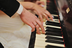 Hands. Of a married couple with wedding rings on a piano Stock Image