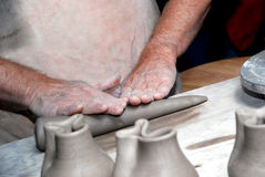 Hands On. A crafter rolling clay for his next project Stock Image