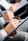 Hands. Row of business people�s hands making a notes in text