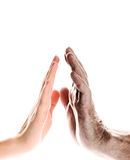Hands. Of young woman and elderly man over white background Royalty Free Stock Image