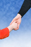 Hands. Close up of mother and daughter holding hands. background of blue sky royalty free stock photography
