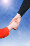 Hands. Close up of mother and daughter holding hands. background of blue sky Stock Photography