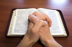 Hands above the bible Stock Photography