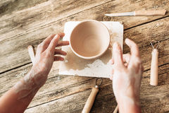 Hands above clay bowl on wooden table, artisan pov Stock Photo