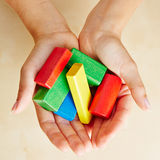 Hands from above holding building blocks stock photos