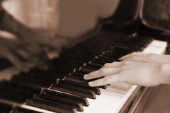 Hands above keys of the piano. Old color Royalty Free Stock Photo