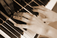 Hands above keys of the piano. Old color Royalty Free Stock Photos