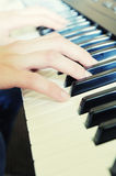 Hands above keys of the piano. Warm color royalty free stock image