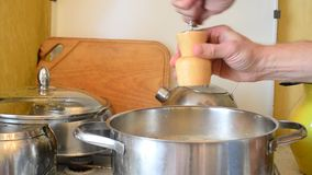 Hands adding pepper into saucepan using pepper mill stock footage