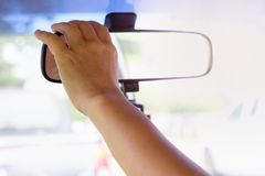 Hands are adjusting the rearview mirror. For good braking and safe car Stock Photography