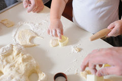 Hands adult, child cook cookies in kitchen closeup. Three pair of Hands make homemade cookies, hands only. Cookie cutters for baking cookies with dough and flour Royalty Free Stock Photos