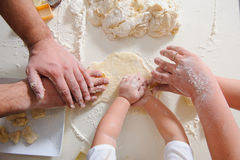 Hands adult, child cook cookies in kitchen closeup. Three pair of Hands make homemade cookies, hands only. Cookie cutters for baking cookies with dough and flour Stock Image