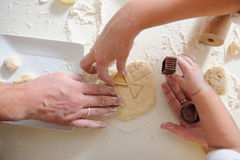 Hands adult, child cook cookies in kitchen closeup. Three pair of Hands make homemade cookies, hands only. Cookie cutters for baking cookies with dough and flour Stock Photo