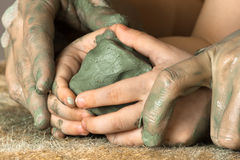 Hands of adult helping child to work with clay Royalty Free Stock Photo