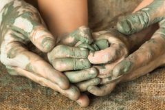 Hands of adult helping child to work with raw clay Stock Image