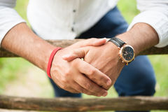 Hands of adult male wearing watch and bracelet Royalty Free Stock Images
