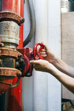 Turning the Valve. The hands of an adult man in the action of turning a bright red valve, part of an industrial plumbing system Stock Images