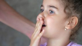 The hands of an adult pull the thread tied to the child`s tooth. Successful attempt to remove a tooth. Pull out the