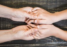Hands of adult woman and little child. Closeup top view of human hands of adult woman and little child isolated on brown wooden background. Flatlay of mother and Royalty Free Stock Images