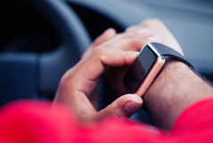 Hands of African man using smart watch sitting in a car Stock Photos