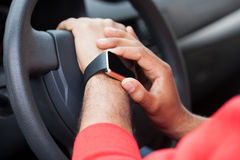 Hands of African man using smart watch sitting in a car Stock Photo
