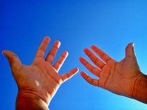 Hands. Against a clear blue sky Stock Images